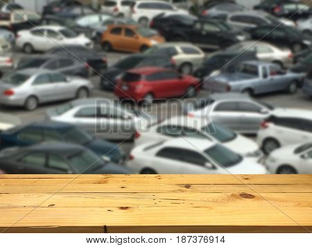 Empty wooden table space platform and blurred outdoor parking lot full of cars background for product display. montage