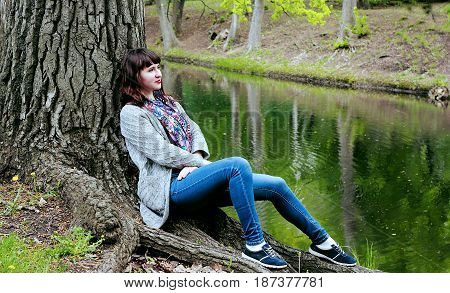 A beautiful girl is resting in the woods on the shore of a small lake.