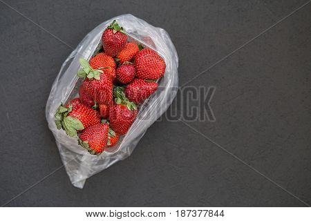 fresh ripe useful fruit strawberry in tray closeup on a black background