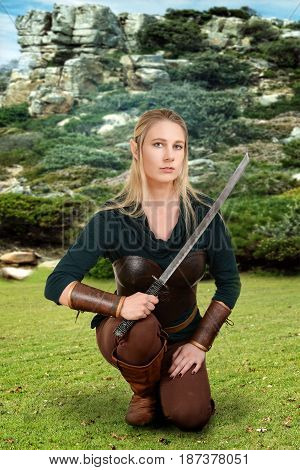 female wood elf kneeling in field holding a sword
