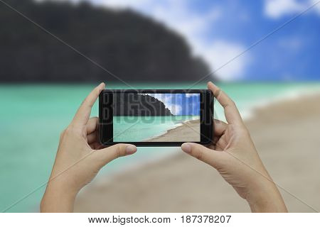 Hand holding smartphone with white blank screen over blurred beachside mountains background.