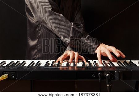 Musician playing the synth on a black background