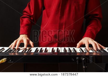 Musician play the keys of the synthesizer on a black background
