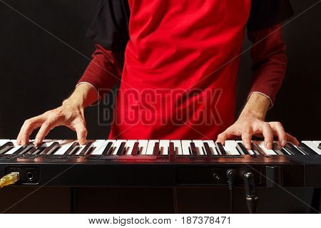 Musician play the keys of the synth on a black background