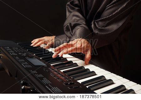 Pianist playing the synthesizer on a black background