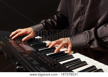 Pianist playing the electronic synthesizer on a black background