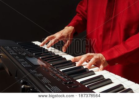 Pianist playing the electronic piano on a black background