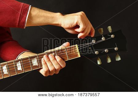 Hands of guitarist tunes the guitar on a dark background
