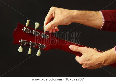 Musician tunes the guitar on a dark background