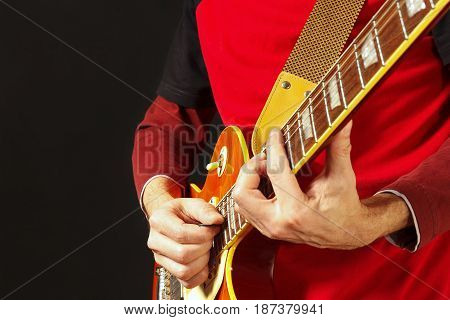 Guitarist playing the electric guitar on a dark background