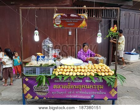 KAMPHAENG PHET THAILAND - MAY 6 : unidentified asian woman with Thai traditional clothing selling mango and sweet sticky rice in Nakhon Chum street market on May 6 2017 in Kamphaeng Phet Thailand.