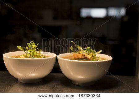 Two Bowls Of Soup Topped With Herbs
