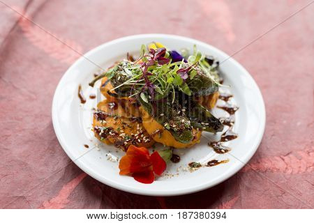 Fritters With Vegetable Topping With Orange Sauce On Round Plate
