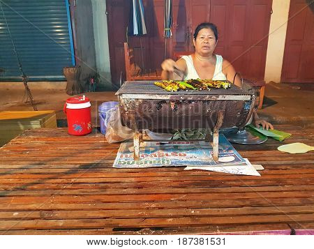 KAMPHAENG PHET THAILAND - MAY 6 : unidentified asian woman with Thai traditional clothing selling grilled dessert in Nakhon Chum street market on May 6 2017 in Kamphaeng Phet Thailand.