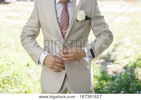 Portrait Of An Attractive Young Businessman Or Bridegroom In Urban Background Wearing White Suit