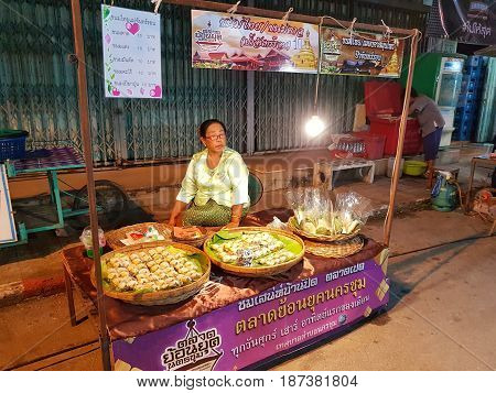 KAMPHAENG PHET THAILAND - MAY 6 : unidentified asian woman with Thai traditional clothing selling Thai dessert in Nakhon Chum street market on May 6 2017 in Kamphaeng Phet Thailand.