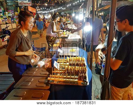 KAMPHAENG PHET THAILAND - MAY 6 : unidentified asian woman with Thai traditional clothing selling food in Nakhon Chum street market at night on May 6 2017 in Kamphaeng Phet Thailand.