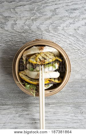 Chopsticks On Vegetarian Chinese Steamed Buns In Bamboo Steamer