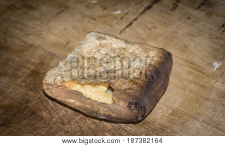 horizontal image of a piece of hardtack bread used in the days of settlers as it would last a long time and not get moldy.