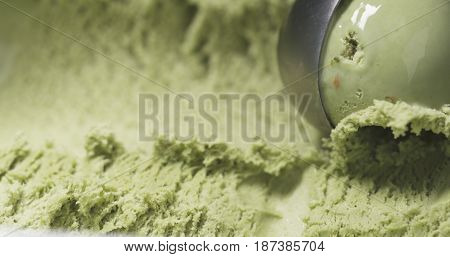 pistachio ice cream being scooped close up, wide photo