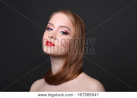 Beauty model on black background with copy space, fashion shooting. Woman with makeup, perfect skin and hair posing to camera at studio