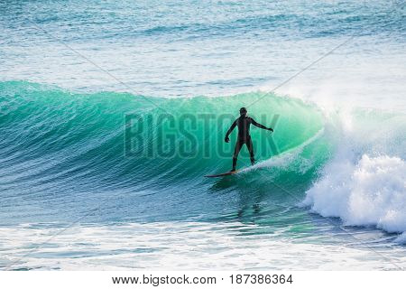 Surfing and big blue wave in ocean. Surfer on wave