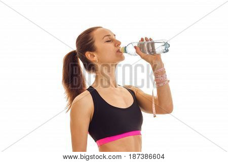young fitness girl stands sideways in the sports top and drinking water from a bottle is isolated on a white background