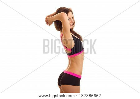young skinny girl stands sideways in sports shorts and top and keeps her hands behind head isolated on white background