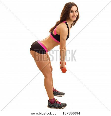 beautiful fitness girl in short shorts stands sideways smiles and leans forward with dumbbells is isolated on a white background