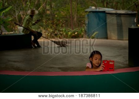 20 April 2016, Chiang Mai Zoo, Thailand. Little girl with mobile and Janitor with a broom sitting under palm tree with mobile phone and listening to music.
