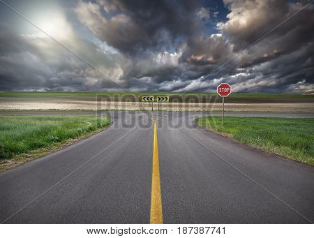 Crossing solution with stop sign towards the sun and clouds with yellow line on asphalt. Success and vision concept.