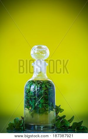 Mint syrup in a glass bottle on a green background