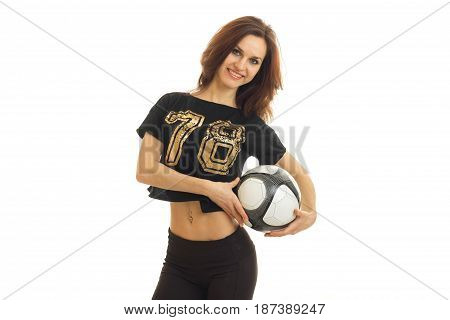 attractive happy girl in t-shirt looks straight and holds the ball isolated on white background