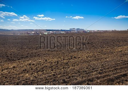 Landscape Black Plowed Field And Blue Sky