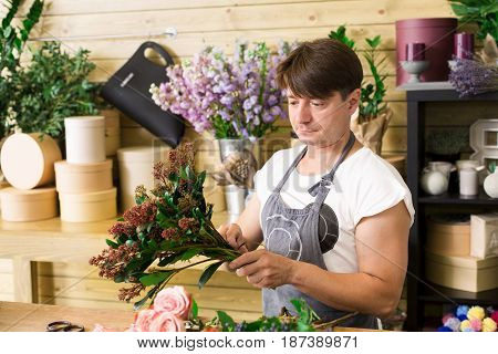 Florist making rose bouquet in flower shop. Man assistant or owner in floral design studio, making decorations and arrangements. Flowers delivery, creating order