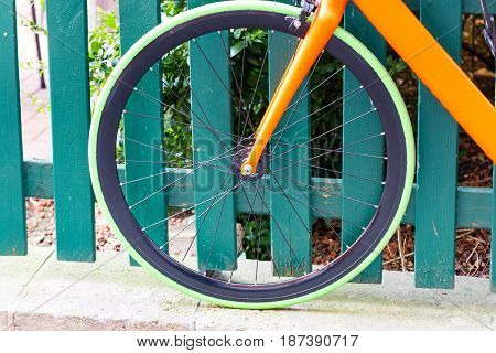 A green tire on a bicycle leaning against a fence