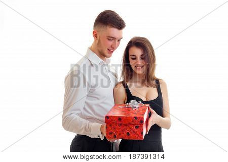 beautiful smiling girl takes red gift that has brought young charming guy isolated on white background