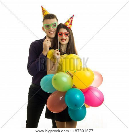 beautiful young couple stand in front of the camera holding a lot of balloons with the requisites and smiling isolated on white background