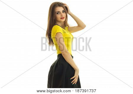 a wonderful young girl in a yellow blouse stands sideways in front of the camera holding a hand near the hair and smiling isolated on white background.