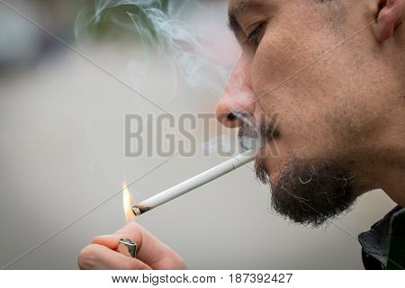 Man pulls a cigarette from the pack and lights up