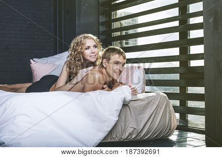 Man and woman couple in their underwear in the bedroom of a beautiful young happy and sexy on the bed