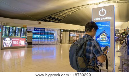 BANGKOK THAILAND - MAR 23 2017: Thai traveler charging mobile phone battery at the free service charging station area at Suvarnabhumi International Airport in Bangkok Thailand.