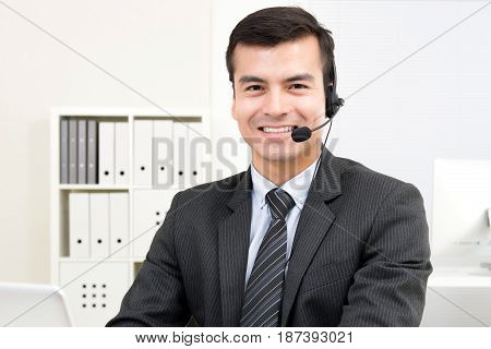 Smiling handsome businessman wearing microphone headset - telemarketing operator call center and customer service staff concepts