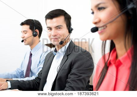 Call center workers wearing microphone headsets - telemarketing operator and customer service concepts