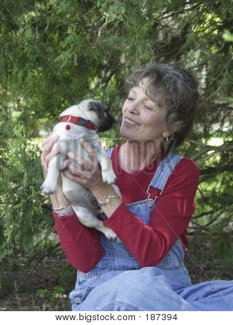 Older Woman Hoding A Puppy