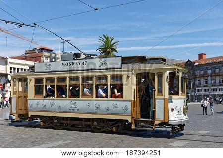 PORTO, PORTUGAL - MAY 8, 2017: People in heritage trams on the Carlos Alberto square. First trams in the city with electric traction were introduced in 1895