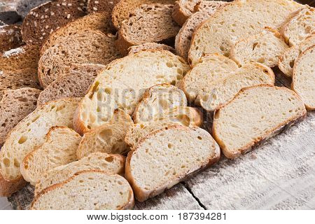 Sliced bread gradient background. Bakery and grocery concept. Fresh, healthy whole grain sliced sorts of rye and white loaves on wood