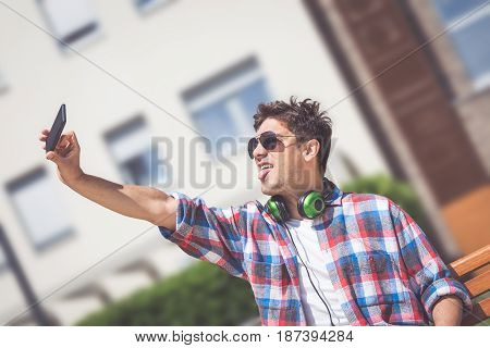 Portrait of young man in casual clothing taking selfie while sitting on a bench outdoors.