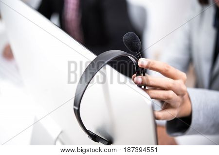 Hand picking up headphone that hanging on computer screen