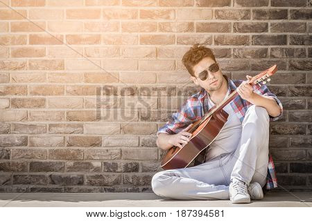 Young urban man sitting on the floor and holding acoustic guitar. Space for copy. Music and modern lifestyle concepts.